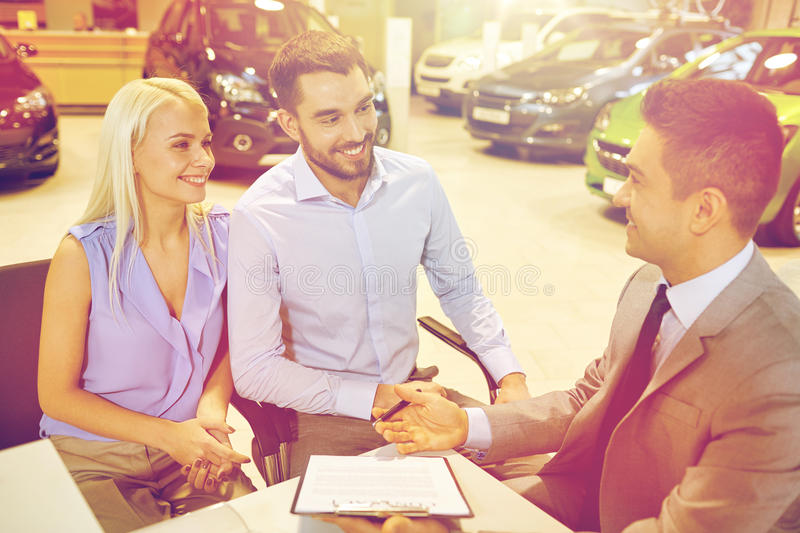 Happy couple with car dealer in auto show or salon. Auto business, sale and people concept - happy couple with dealer buying car in auto show or salon stock photos