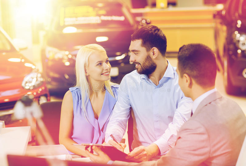 Happy couple with car dealer in auto show or salon. Auto business, sale and people concept - happy couple with dealer buying car in auto show or salon royalty free stock image
