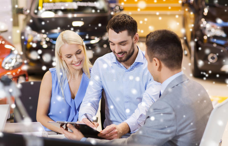 Happy couple with car dealer in auto show or salon. Auto business, sale and people concept - happy couple with dealer buying car in auto show or salon over snow stock image
