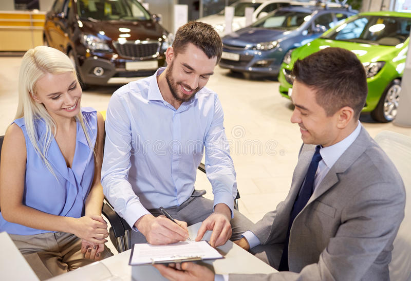 Happy couple with car dealer in auto show or salon. Auto business, sale and people concept - happy couple with dealer buying car and signing documents in auto stock image