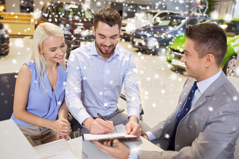 Happy couple with car dealer in auto show or salon. Auto business, sale and people concept - happy couple with dealer buying car and signing documents in auto royalty free stock photo