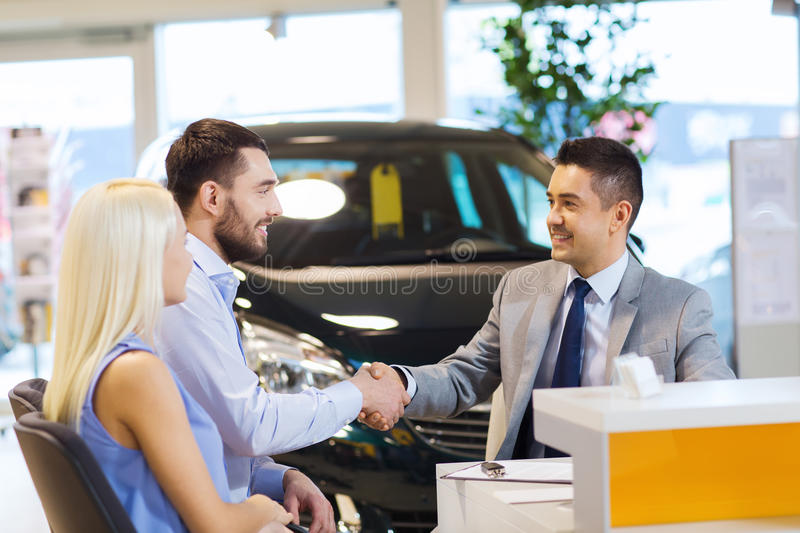 Happy couple with car dealer in auto show or salon. Auto business, car sale, and people concept - happy couple with dealer shaking hands in auto show or salon royalty free stock images