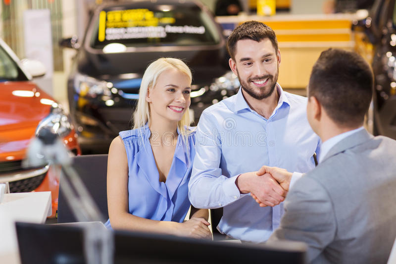 Happy couple with car dealer in auto show or salon. Auto business, car sale, and people concept - happy couple with dealer shaking hands in auto show or salon royalty free stock photography