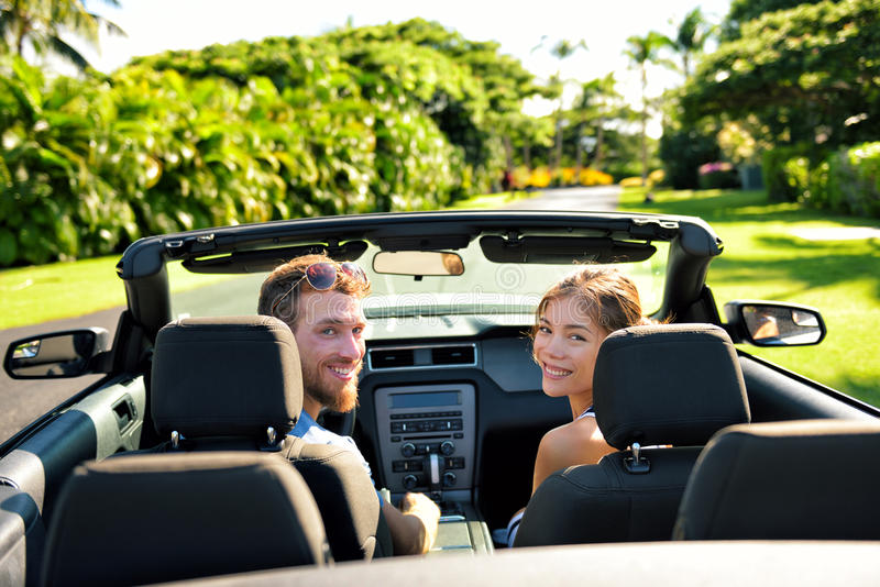 Happy couple in car on summer road trip travel. Multiracial young couple carefree on holidays driving a convertible cabriolet automobile on the roadway in the stock photo