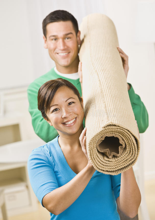 Happy Couple Carrying Carpet Roll royalty free stock photography
