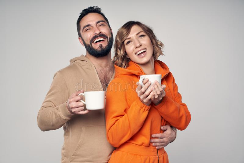 Happy couple in casual clothes standing with tea cups. Smiling at camera royalty free stock image