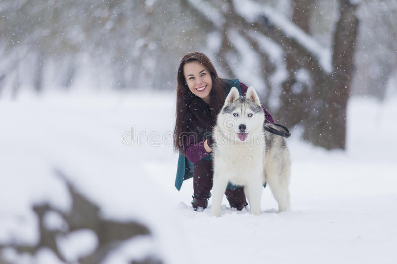 Happy Couple of Caucasian Brunette Woman Happy Smiling and Her Husky Dog. royalty free stock photography