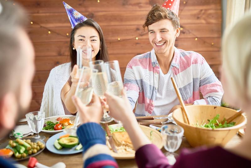 Happy Couple Celebrating Birthday at Dinner. Smiling young couple of happy young people wearing holiday caps celebrating Birthday with friends clinking champagne stock image