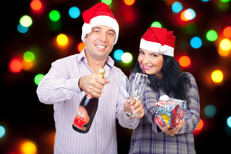 Happy couple celebrating Christmas. Night and invite you to join the fun with champagne ,glasses and a gift royalty free stock images