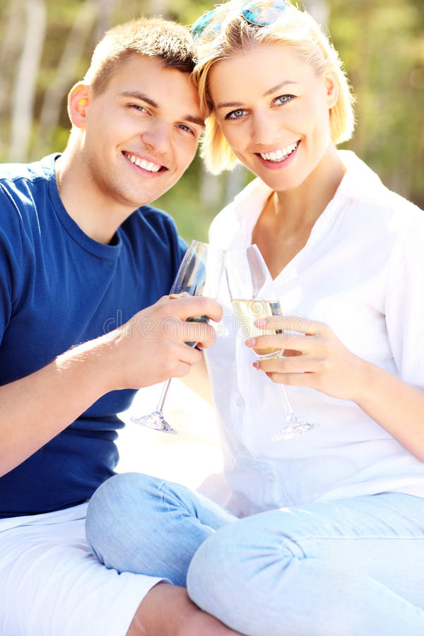 Happy couple and champagne. A picture of an adult couple with glasses of champagne at the beach stock photo