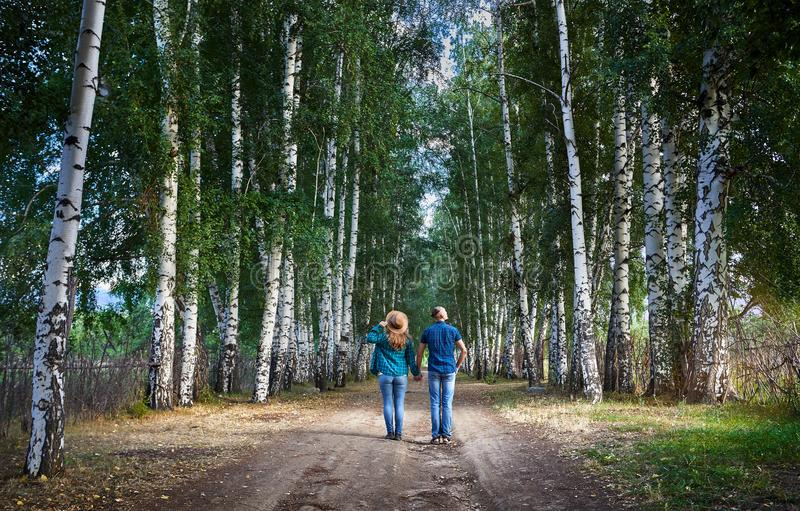 Hipster couple in the birch wood. Happy couple in checked shirts on the road in birch wood in Kyrgyzstan. Romantic date in the forest stock photography