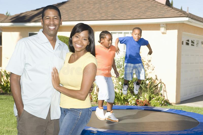 Happy Couple With Children Playing On Trampoline stock photography