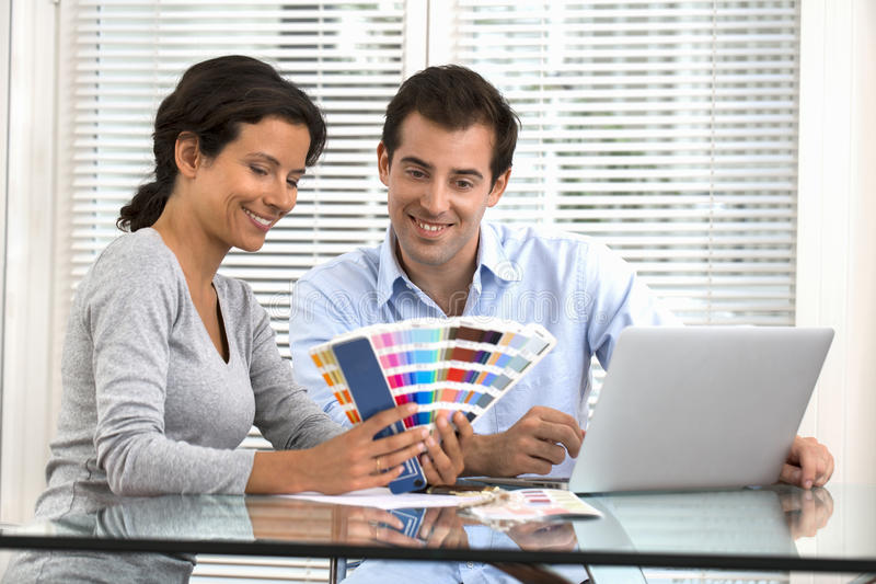 Happy couple choosing colors to paint new house royalty free stock photography