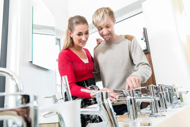 Happy couple choosing a new faucet in a modern sanitary ware shop. Low-angle portrait of a happy couple choosing a new faucet for their bathroom in a modern stock image