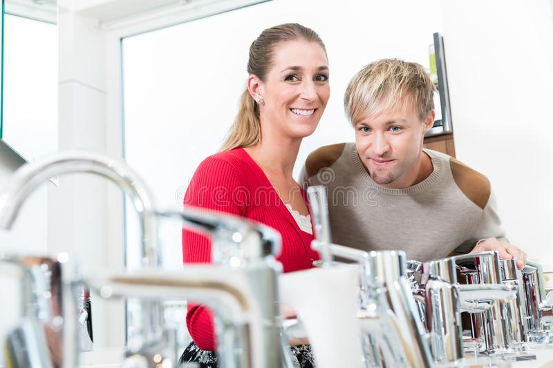 Happy couple choosing a new faucet in a modern sanitary ware shop. Low-angle portrait of a happy couple choosing a new faucet for their bathroom in a modern royalty free stock images