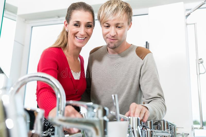 Happy couple choosing a new faucet in a modern sanitary ware shop. Low-angle portrait of a happy couple choosing a new faucet for their bathroom in a modern stock images