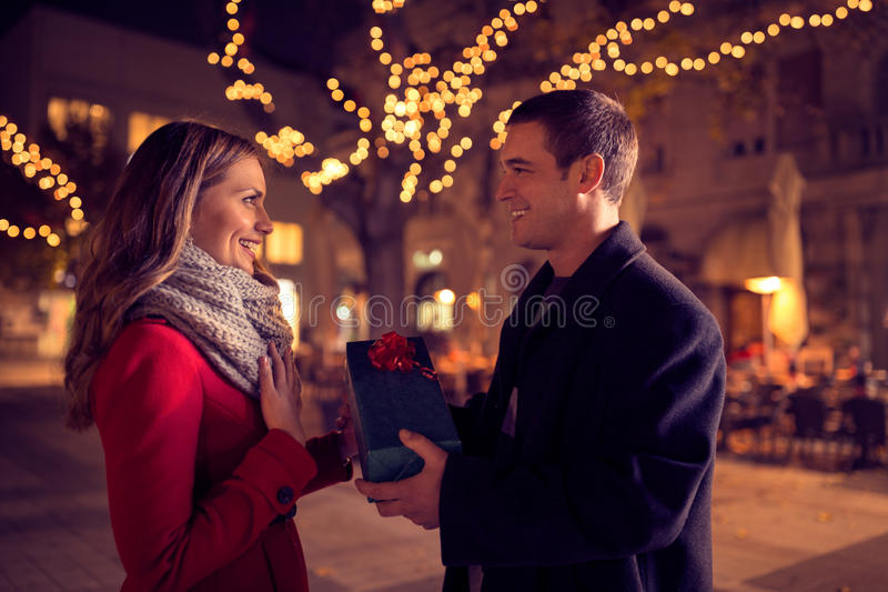 Happy couple with Christmas and New Year gift on street stock photo