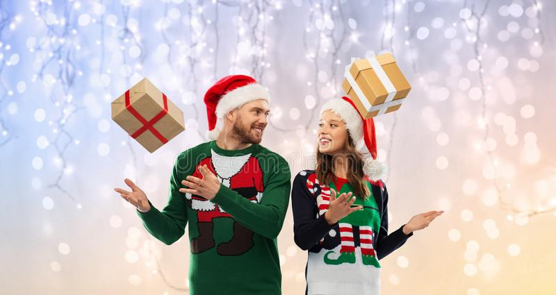 Happy couple in christmas sweaters with gifts. People and holidays concept - happy couple in santa hats with christmas gifts at ug sweater party over festive stock images