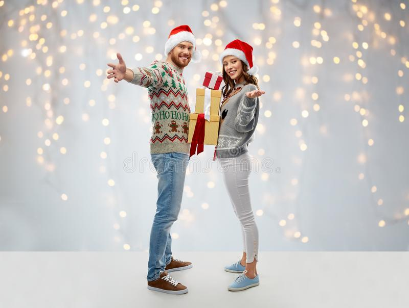 Happy couple in christmas sweaters with gifts royalty free stock image