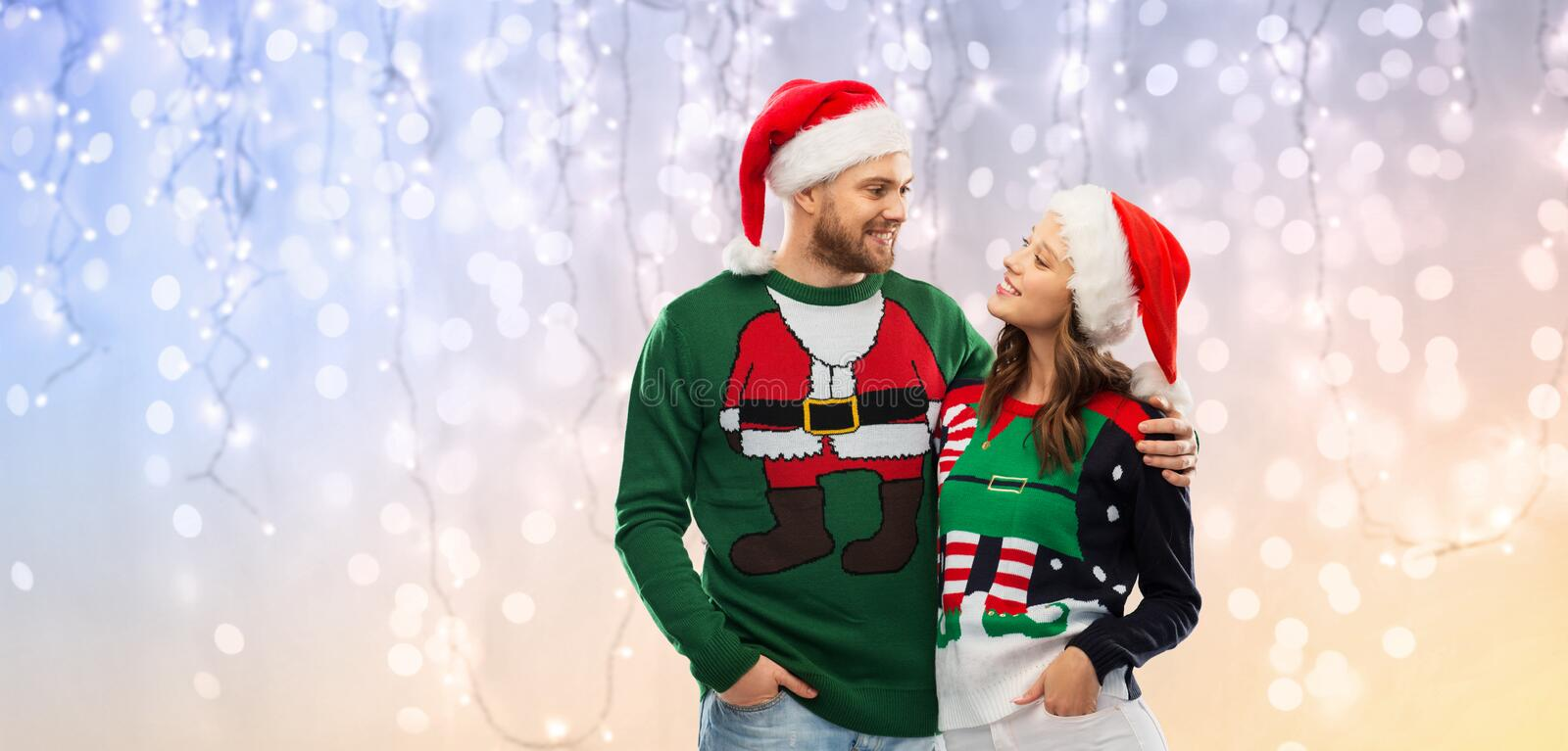 Happy couple in christmas sweaters and santa hats. Christmas, people and holidays concept - portrait of happy couple in santa hats at ug sweater party over royalty free stock images