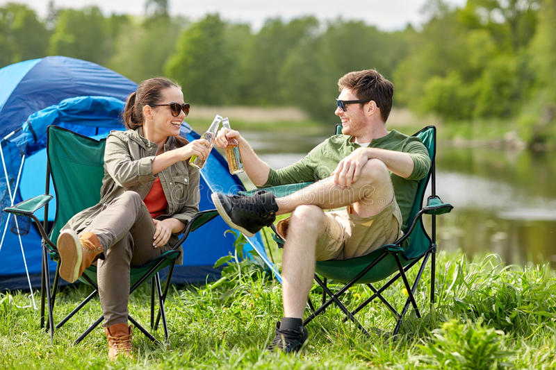 Happy couple clinking drinks at campsite tent. Camping, travel, tourism, hike and people concept - happy couple clinking beer bottles at campsite tent royalty free stock photo