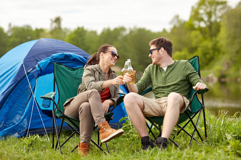 Happy couple clinking drinks at campsite tent. Camping, travel, tourism, hike and people concept - happy couple clinking beer bottles at campsite tent royalty free stock photos