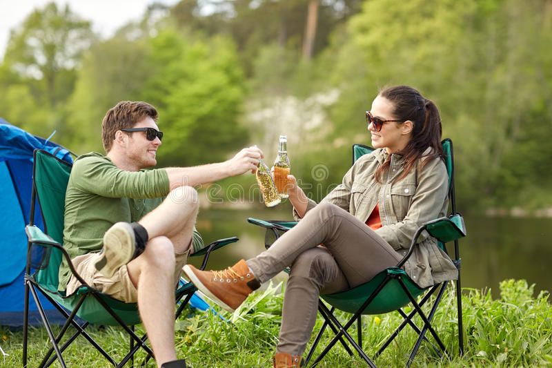 Happy couple clinking drinks at campsite tent. Camping, travel, tourism, hike and people concept - happy couple clinking beer bottles at campsite tent stock photo