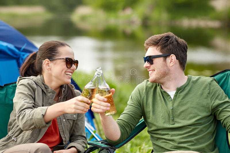 Happy couple clinking drinks at campsite tent. Camping, travel, tourism, hike and people concept - happy couple clinking beer bottles at campsite tent stock photos