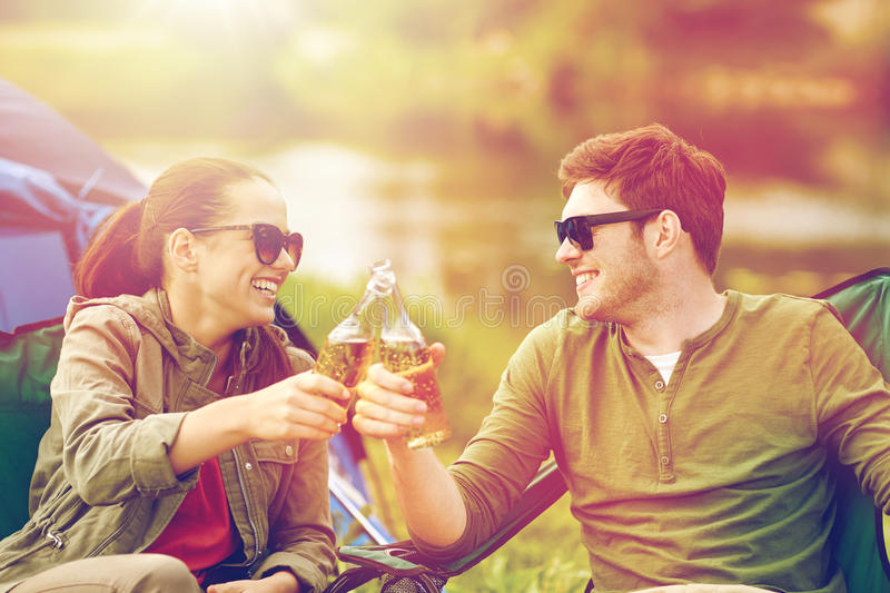 Happy couple clinking drinks at campsite tent. Camping, travel, tourism, hike and people concept - happy couple clinking beer bottles at campsite tent stock photography