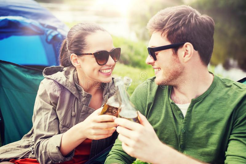 Happy couple clinking drinks at campsite tent. Camping, travel, tourism, hike and people concept - happy friends clinking glass bottles and drinking cider or royalty free stock photo