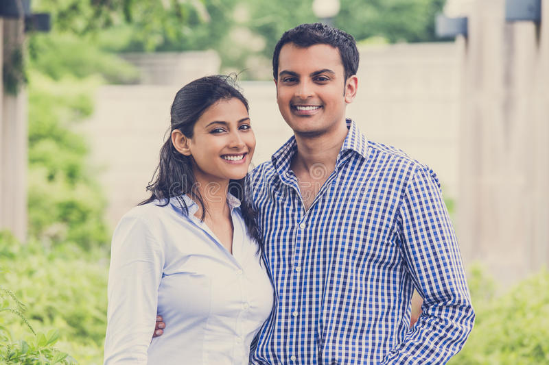 Happy couple. Closeup portrait, attractive wealthy successful couple in blue shirt and striped outfit holding each other smiling, isolated outside green trees stock image