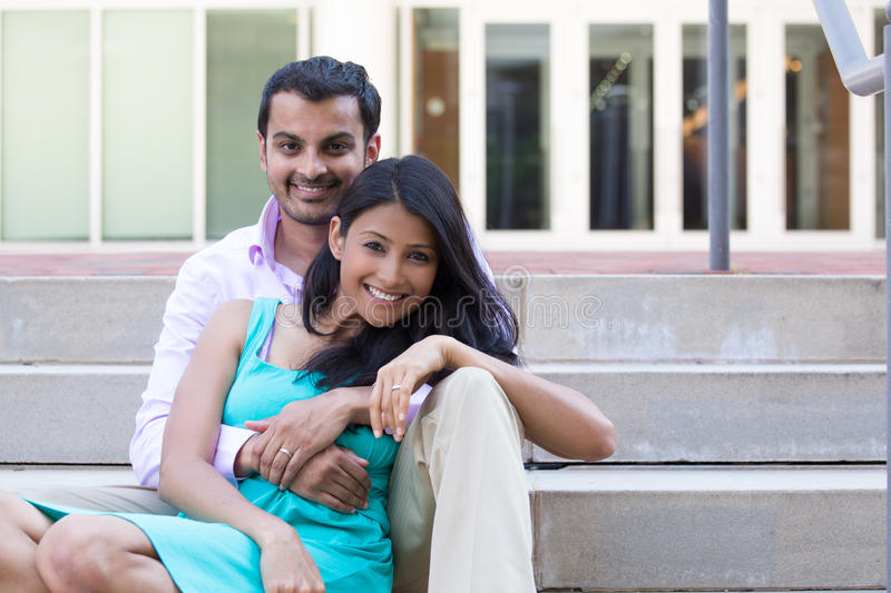 Happy couple. Closeup portrait, attractive wealthy successful couple in pink shirt and green dress holding each other smiling, isolated outside stairwell royalty free stock photos