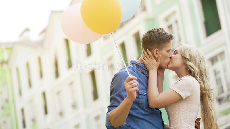 Happy couple with colorful air balloons kissing in street, tender relationship stock image