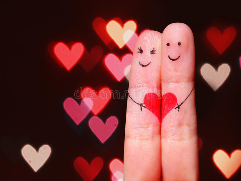 Happy Couple Concept. Two fingers in love with painted smiley. Faces and heart over bokeh background stock images