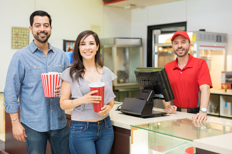 Happy couple in a concession stand. Portrait of a good looking Hispanic couple getting some snacks at the concession stand in a movie theater and smiling royalty free stock images