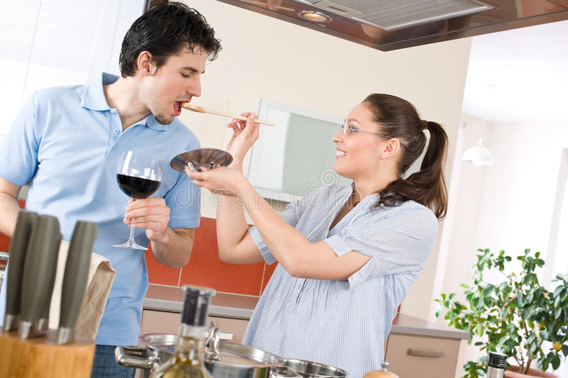 Happy couple cook in kitchen tasting food royalty free stock photography