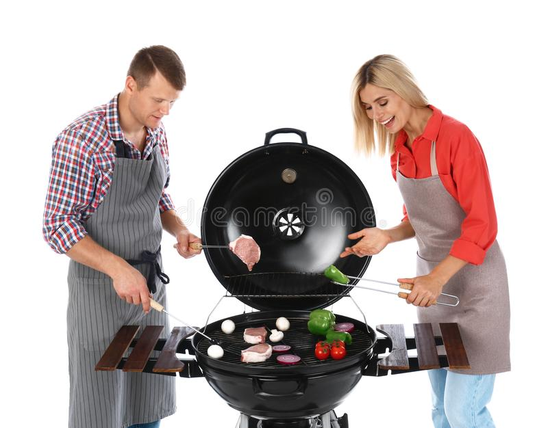 Happy couple cooking on barbecue grill,  background. Happy couple cooking on barbecue grill, white background stock photography