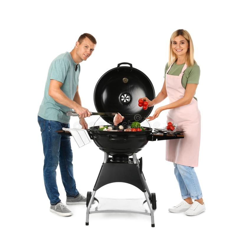 Happy couple cooking on barbecue grill royalty free stock photography