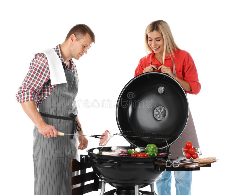 Happy couple cooking on barbecue grill. White background royalty free stock photos