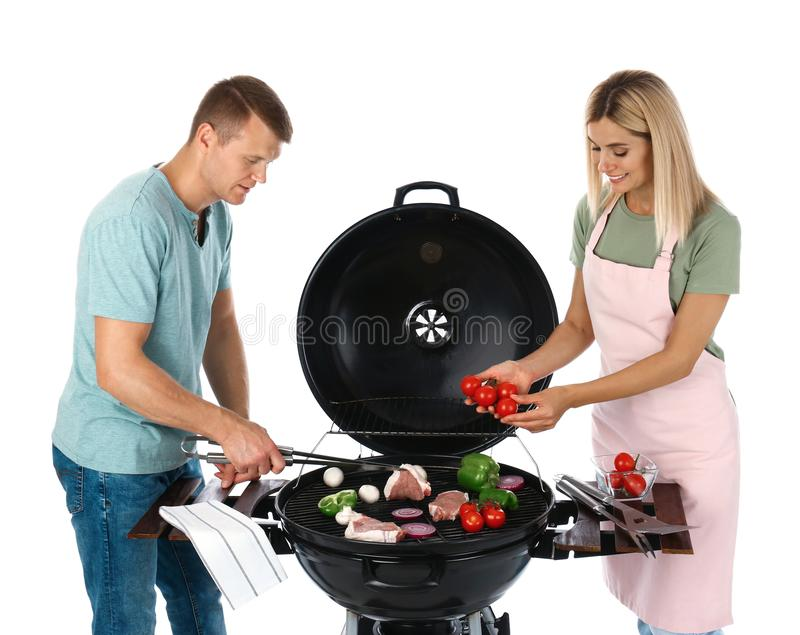 Happy couple cooking on barbecue grill. White background royalty free stock images
