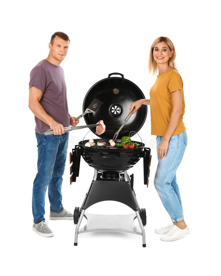 Happy couple cooking on  grill, white background stock image