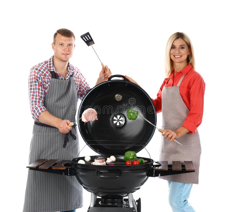 Happy couple cooking on  grill, white background. Happy couple cooking on barbecue grill, white background royalty free stock image