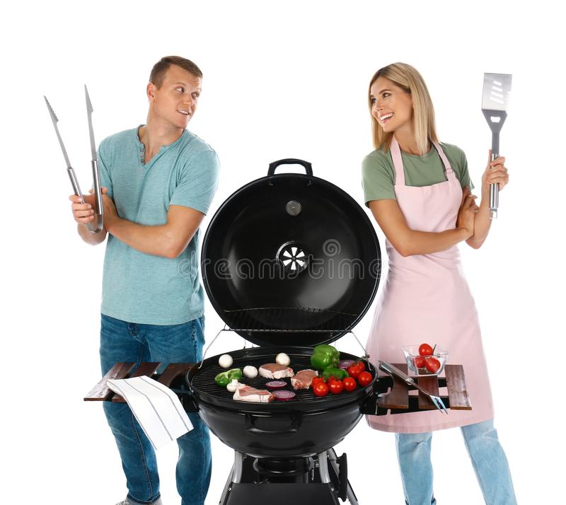 Happy couple cooking on barbecue grill, white. Background royalty free stock images