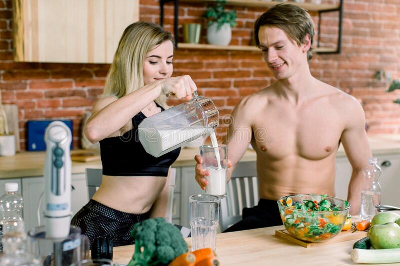Happy couple cooking dinner together and drinking milk in their loft kitchen at home, stock photography