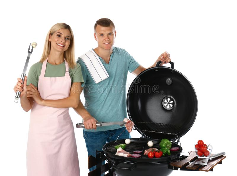 Happy couple cooking on  grill, white background. Happy couple cooking on barbecue grill, white background stock photo