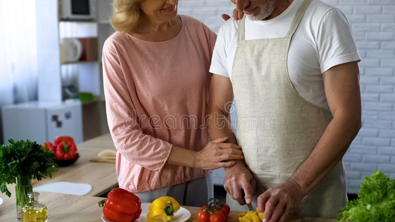 Happy couple cooking healthy dinner at home kitchen, romantic moments together royalty free stock image