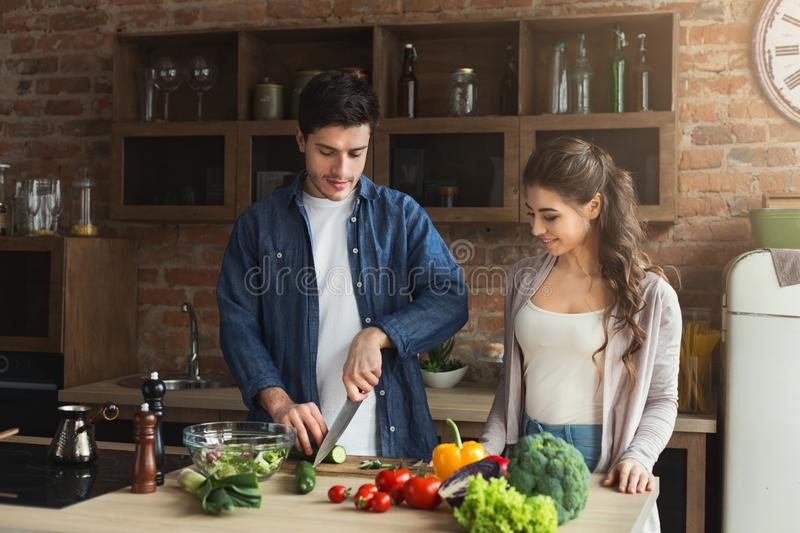 Happy couple cooking healthy food together stock photo