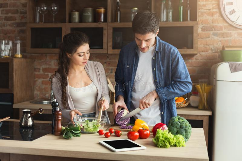 Happy couple cooking healthy food together stock image