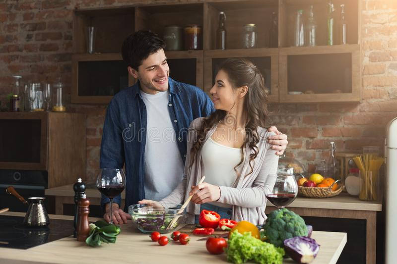 Happy couple cooking healthy food together stock photography