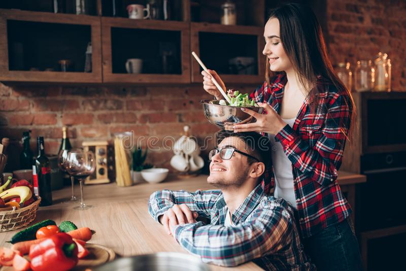 Happy couple cooking vegetable salad together royalty free stock photography